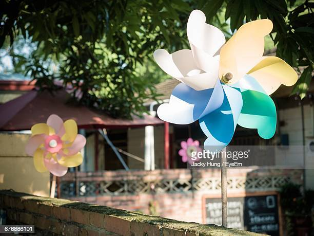 Pinwheels On Retaining Wall Against Houses