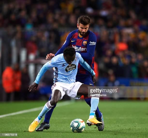 Pione Sisto of RC Celta de Vigo controls the ball under pressure from Gerard Pique of FC Barcelona during the La Liga match between FC Barcelona and...