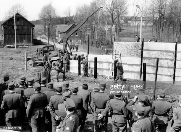 Pioneers of the Soviet zone People's Army start to build a new barrier wall in the divided village Moedlareuth in 1966 In the foreground a group of...