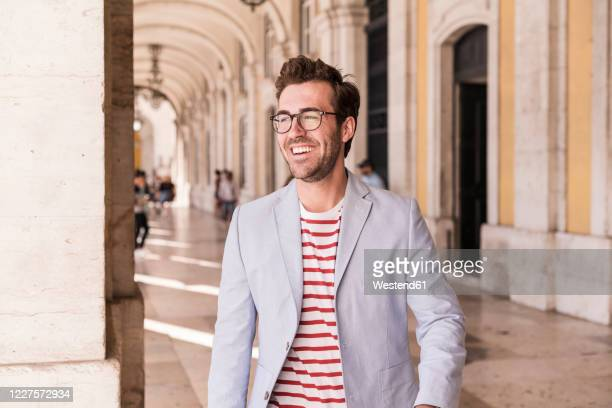 piortrait of happy young man in the city, lisbon, portugal - brown hair stock pictures, royalty-free photos & images