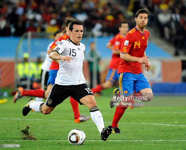 Piotr Trochowski of Germany with Xabi Alonso of Spain during the 2010 FIFA World Cup South Africa Semi Final match between Germany and Spain at...