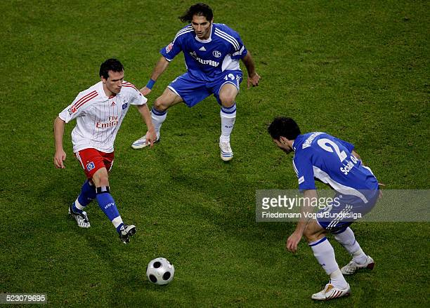 Piotr Trochowski of Hamburg challenges Halil Altintop and Heiko Westermann of Schalke for the ball during the Bundesliga match between Hamburger SV...
