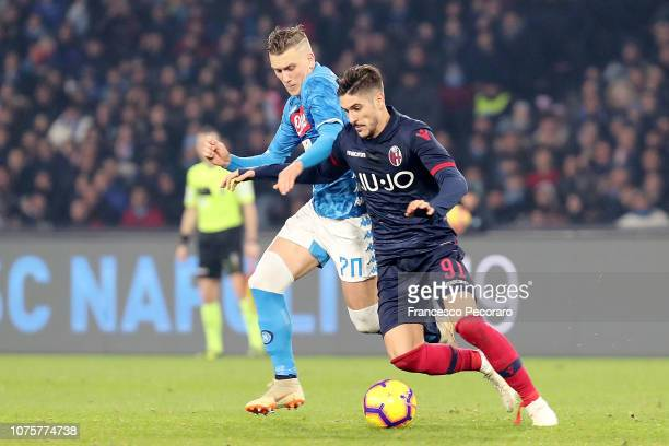 Piotr Zielinski of SSC Napoli vies Diego Falcinelli of Bologna FC during the Serie A match between SSC Napoli and Bologna FC at Stadio San Paolo on...