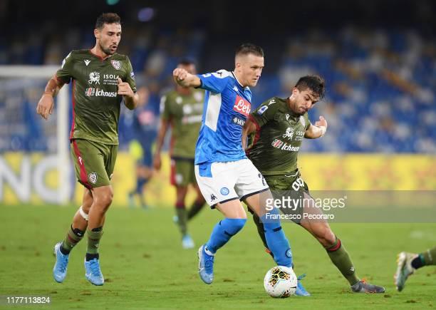 Piotr Zielinski of SSC Napoli vies with Giovanni Simeone of Cagliari Calcio during the Serie A match between SSC Napoli and Cagliari Calcio at Stadio...
