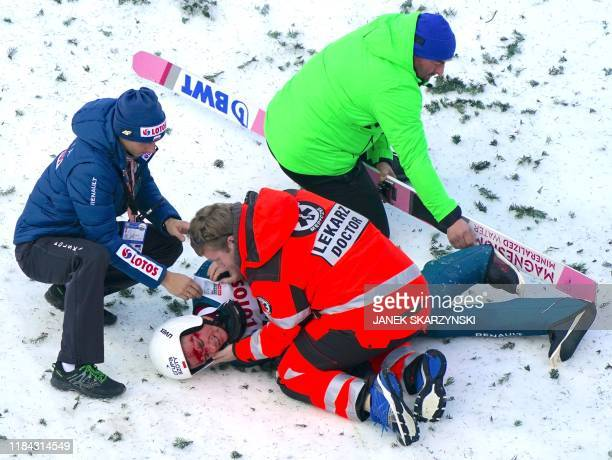 Piotr Zyla of Poland gets medical assistance after he has fallen during the FIS Ski Jumping World Cup in Wisla, Poland on November 24, 2019.