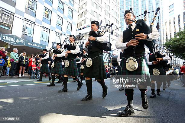 A pipe band marches during the Anzac Day eve street parade on April 24 2015 in Wellington New Zealand The parade was organised to remember the...