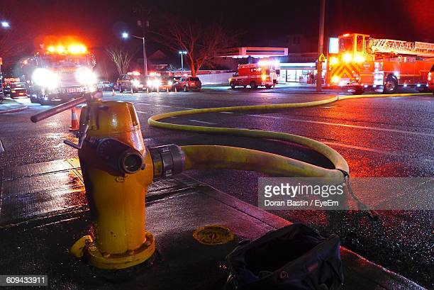 Pipe Connecting Fire Hydrant By Emergency Vehicles On Street At Night
