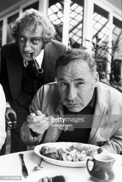 A pipe in his mouth English actor and comedian Marty Feldman stands behind film director actor and comedian Mel Brooks the latter of whom eats a meal...