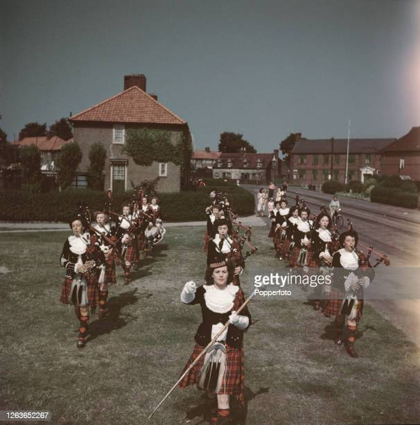 Pipe Major Peggy Iris leads the Dagenham Girl Pipers pipe band in a practice session of part of their repertoire through a housing estate in England...