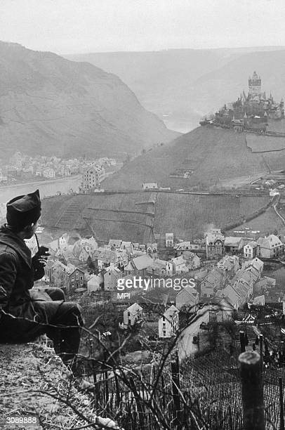 A pipe smoking 'doughboy' takes a quiet moment to view a German town spread in the valley below and the castle perched on an adjoining hilltop