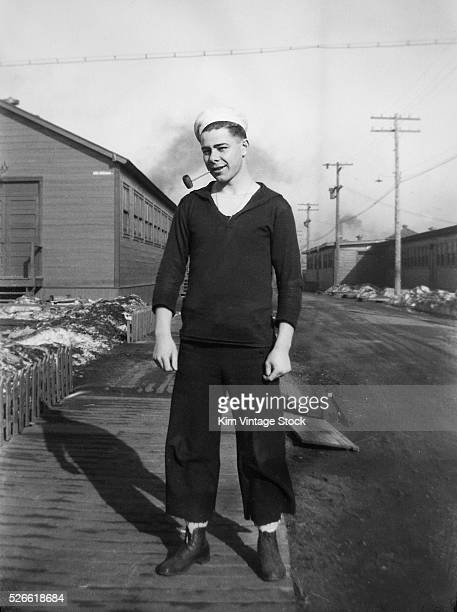 A pipe smoking sailor stands on the grounds of Great Lakes Naval Training Station