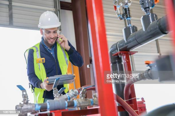 pipeline engineer making call while inspecting oil and gas equipment - centrifugador imagens e fotografias de stock
