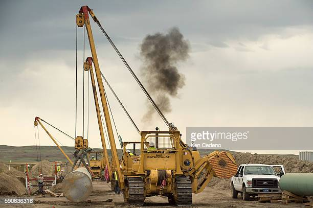 US Pipeline workers guides a crane operator with a new section of natural gas pipe near Bainville MT Sept 17 2013 US Pipeline Inc out of Houston TX...