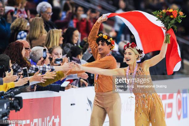 Piper Gilles and Paul Poirier of Canada take their victory lap with the Canadian flag placing first in the ice dance during the ISU Grand Prix of...