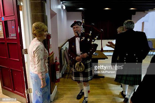 A piper greeting guests arriving for a St Andrew's dinner dance held by the Sandbach and District Caledonian Society at Sandbach Town Hall Cheshire...