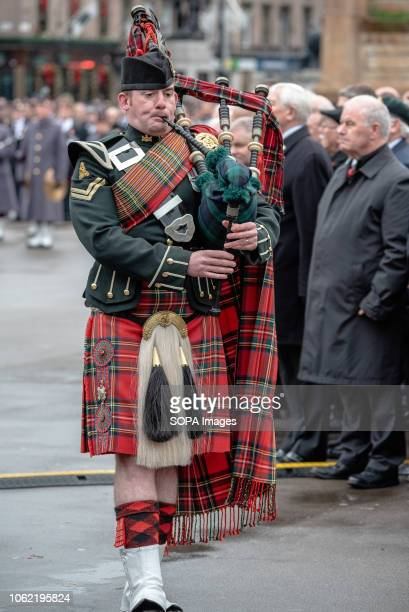 A piper is seen playing the bagpipes during the remembrance day procession in George Square Glasgow Members of the UK armed forces Police Scotland...