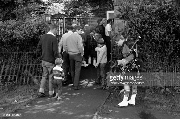 Piper playing for tourists queueing to enter Woburn Abbey and Gardens in Bedfordshire, circa July 1969. From a series of images to illustrate the...