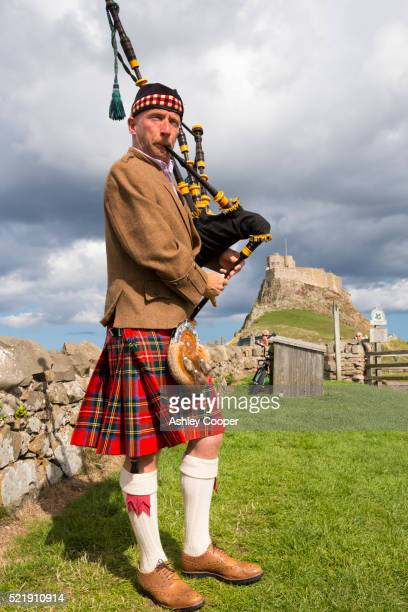 A piper playing outside Lindisfarne Castle, Holy Island, Northumberland, UK.