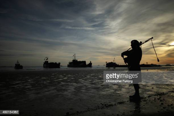 A piper plays a lament on Gold Beach as landing craft from the Royal Marines arrive at Arromanche on June 6 2014 in Arromanches Les Bains France...