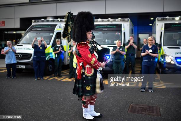 Piper plays as NHS staff at the Queen Elizabeth Hospital participate in the Clap for Carers and key workers after month of lockdown on April 23 in...