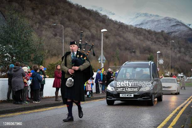 Piper plays as the funeral cortege of Dr Hamish MacInnes OBE BEM, mountaineer as it makes its way through Glencoe on December 4, 2020 in Glencoe,...