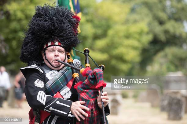 Piper Tosh McDonald plays the bagpipes as the coffin of World War 2 veteran Patrick Churchill in carried from the War Memorial on Church Green...