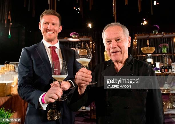Piper-Heidsieck Business Development Manager Kyle Kaplan and US-Austrian chef Wolfgang Puck pose with glasses of Champagne during the 92nd Annual...