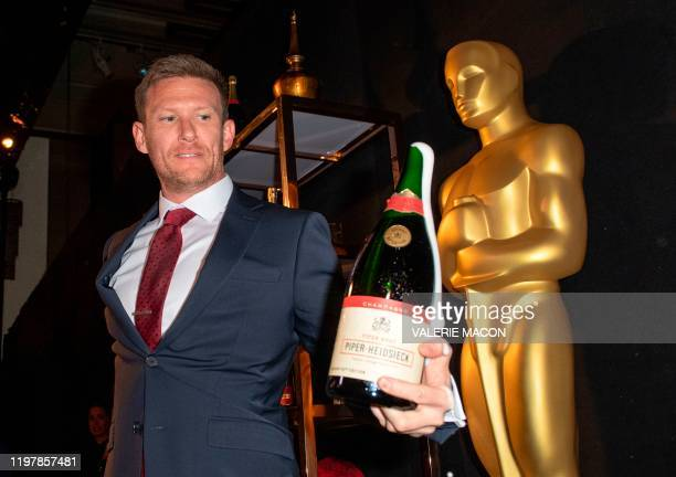 Piper-Heidsieck Business Development Manager Kyle Kaplan holds a bottle of Champagne which he opened with a saber at the 92nd Annual Academy Awards...