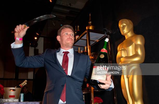 Piper-Heidsieck Business Development Manager Kyle Kaplan opens a bottle of Champagne with a saber at the 92nd Annual Academy Awards Governors Ball...