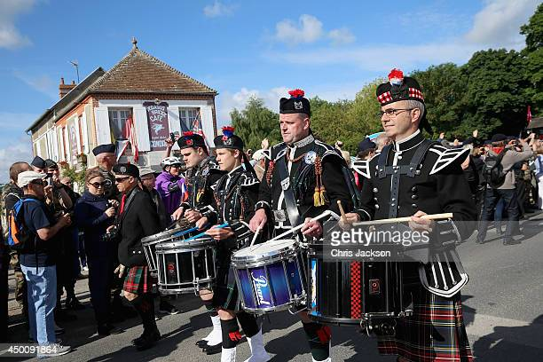 Pipers march past Cafe Gondree the Pegasus Bridge Cafe the first house in France to be liberated during the last hour of 5th June 1944 during DDay...