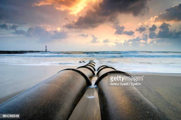 pipes at beach against sky during sunset - pipeline stock pictures, royalty-free photos & images