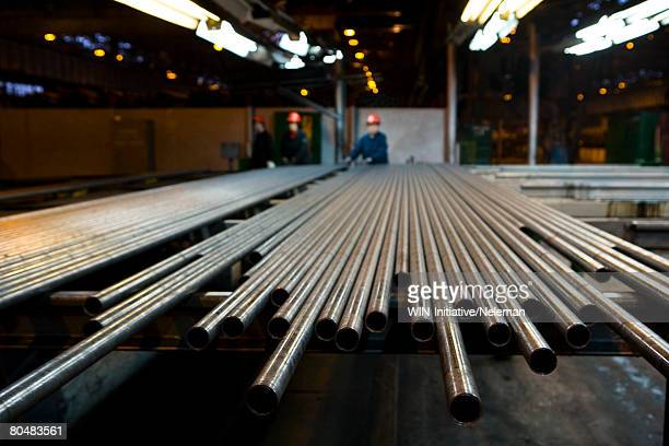 pipes in row with workers in steel factory - steel stock pictures, royalty-free photos & images