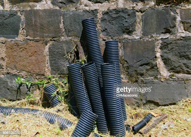 Pipes of power cables coming out of the ground on days of scorching sun next to a wall of stones.