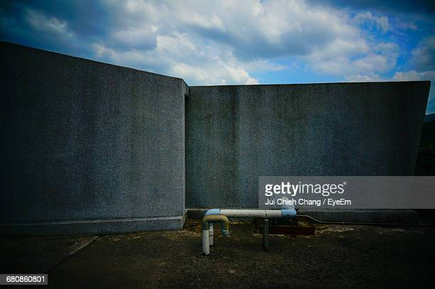 pipes on field connected with wall in factory against sky - chang jui chieh imagens e fotografias de stock