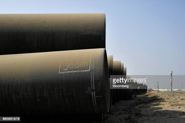 Pipes sit stacked at the project site for a 920squarekilometer industrial area located on the DelhiMumbai Industrial Corridor near the village of...