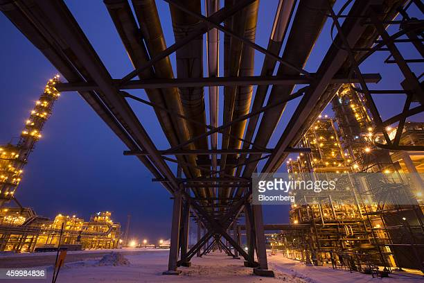 Pipework passes overhead between illuminated petroleum cracking tower units at the LukoilNizhegorodnefteorgsintez oil refinery operated by OAO Lukoil...