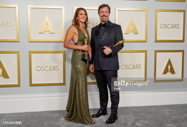 """Pippa Ehrlich and James Reed, winners of Best Documentary Feature for """"My Octopus Teacher"""", pose in the press room during the Oscars on Sunday, April..."""