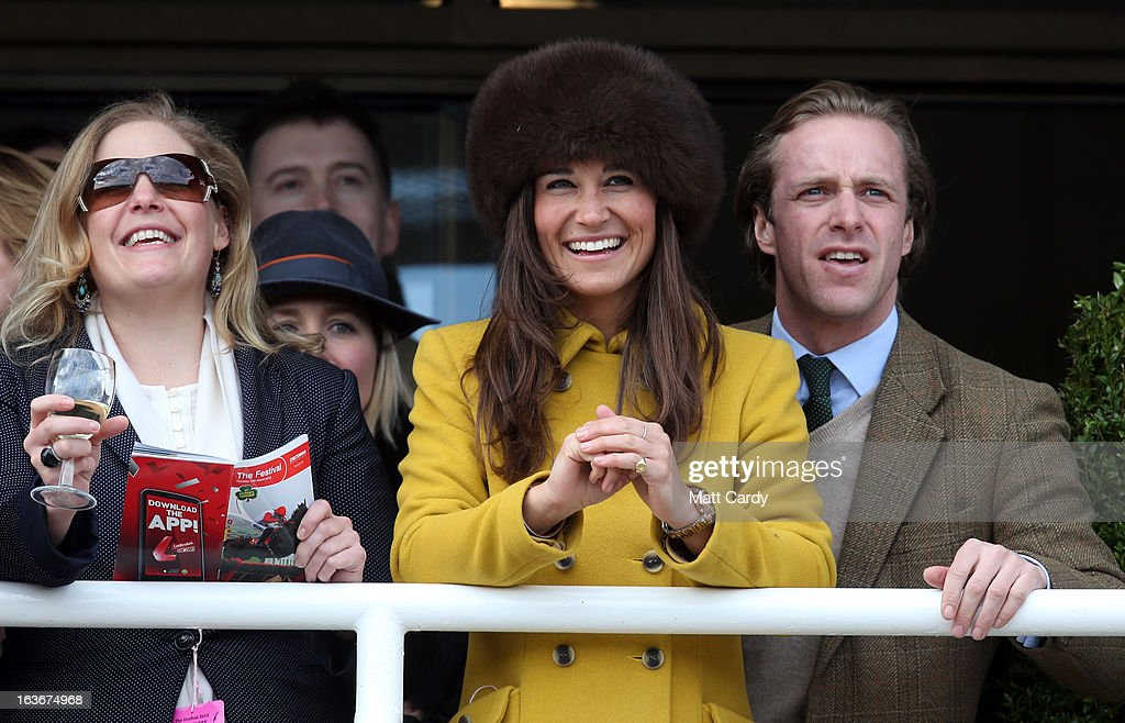 Pippa Middleton (C) and Tom Kingston (R) watch the races at Cheltenham Racecourse on the third day of the Cheltenham Festival 2013 on March 14, 2013 in Cheltenham, England. Approximately 200,000 racing enthusiasts are expected at the four-day festival, which opened on Tuesday and is seen as many as the highlight of the jump racing calendar.