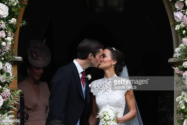Pippa Middleton kisses her new husband James Matthews, following their wedding ceremony at St Mark's Church in Englefield, west of London, on May 20,...