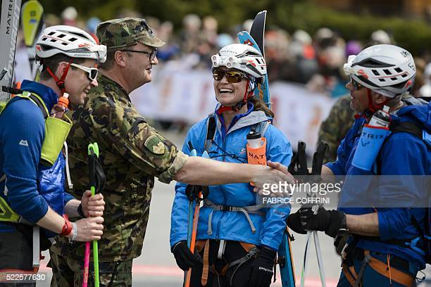 Pippa Middleton smiles next to her teammates Tarquin Cooper and Bernie Shrosbree as they are congratulated by an unidentified Swiss army officer...