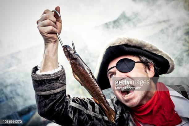 Pirat mit Augenklappe hat einen geräucherten Fisch am Haken