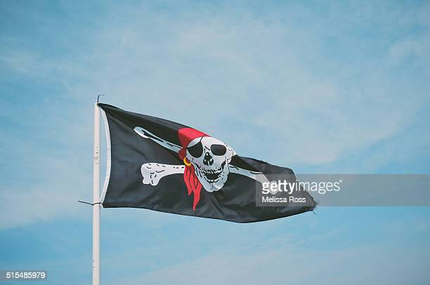 Pirate flag or Jolly Roger flying against blue sky