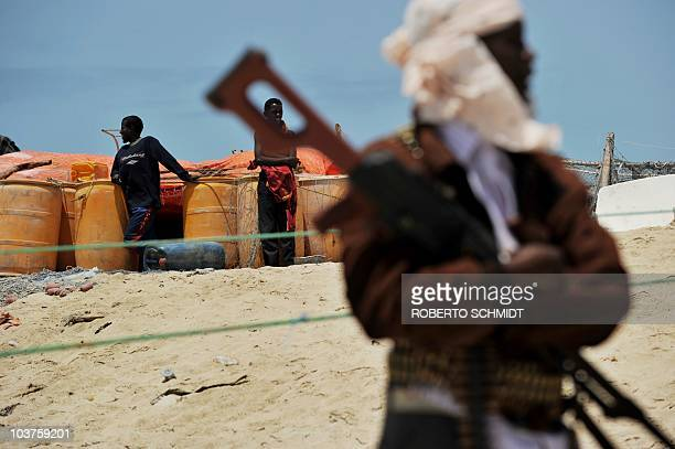 Pirate folds his arms over his high-caliber weapon near two boys standing next to plastic drums filled with gasoline on a beach in the central Somali...