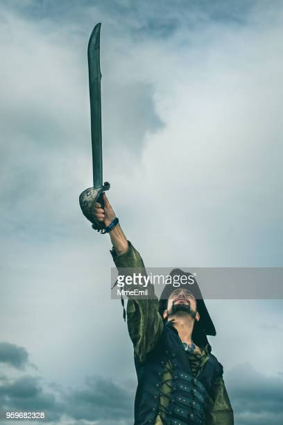 pirate holding a sword in a storm - tricornered hat stock photos and pictures