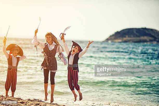 pirate kids jumping with joy on the beach - female pirate stock photos and pictures