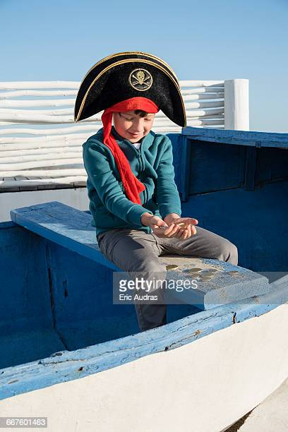 Pirate little boy holding coins on boat