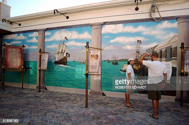 Pirate Museum Manager Jeff Sorg speaks with a mural artist outside the Pirate Soul Museum10 January 2005 in Key West Florida The mural depicts Port...