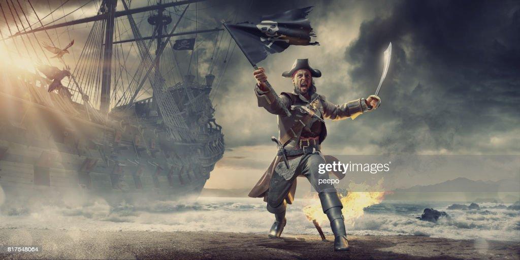 Pirate On Beach Holding Flag and Cutlass Near Pirate Ship : Stock Photo