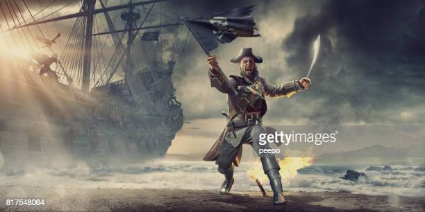 pirate on beach holding flag and cutlass near pirate ship - pirate ship stock photos and pictures