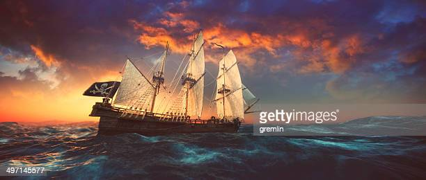 pirate ship sailing on the open seas at sunset - pirate ship stock photos and pictures
